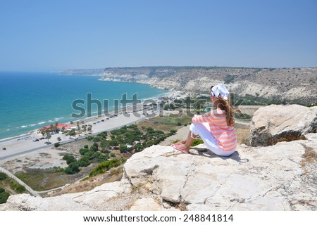 Girl on the rock looking to the ocean. Cyprus - stock photo