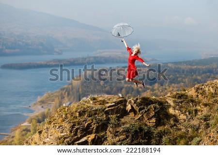 girl on the rock umbrella, jump - stock photo