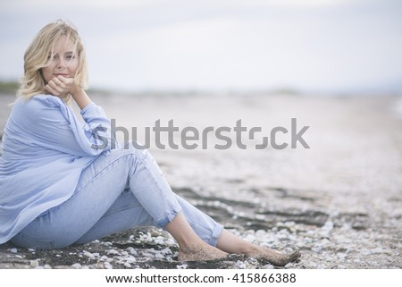 """Girl on the sand. The ease of mind. Woman enjoying the sea breeze , sea and sand . Smiles , do not think of """"tomorrow"""" . - stock photo"""