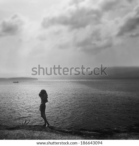 girl on the shore of a beautiful lake, fine art - stock photo