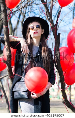 Girl on the street among trees and red balls. The hat and glasses