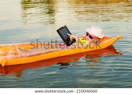 girl on the swimming mattress with laptop - stock photo
