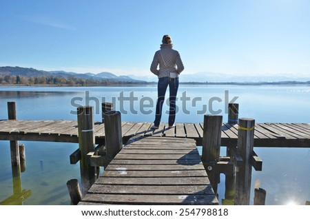 Girl on the wooden jetty at a lake. Switzerland - stock photo