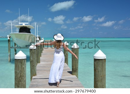 Girl on the wooden jetty looking to the ocean. Great Exuma, Bahamas - stock photo