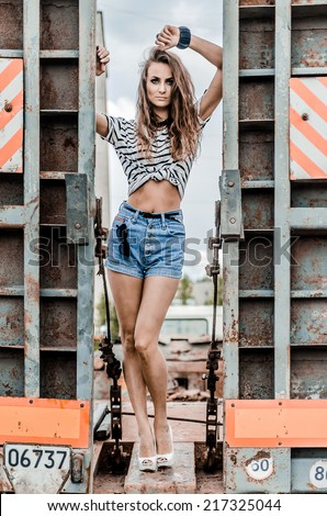 Girl on thr truck in blue shorts and white high heels - stock photo