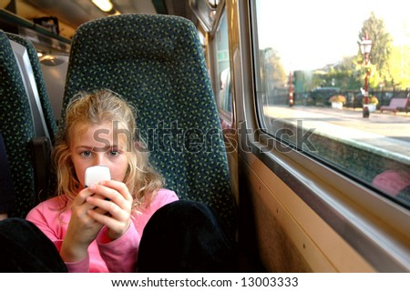 girl on train playing with mobile phone - stock photo