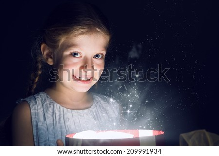 girl opens a box of magic, sorcery, and there shines the light, Christmas miracle - stock photo