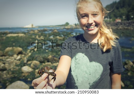 girl or teen holding a small crab standing near tidal pools at Tillamook bay Oregon.