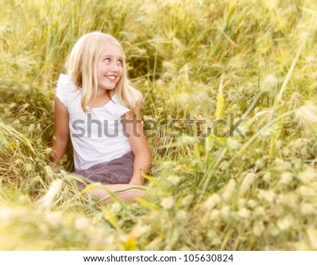 Girl or teen sitting in wheat field looking over - stock photo