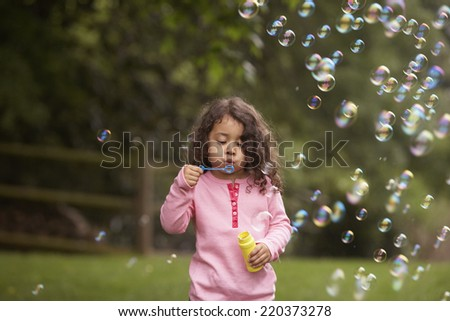 Girl outdoors blowing bubbles - stock photo