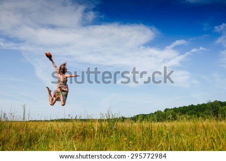 Girl Outdoors enjoying nature. Fun jump Summer time - stock photo