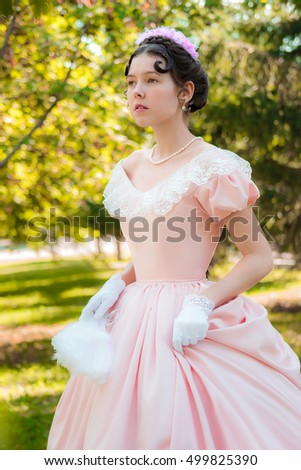 Girl outdoors in evening dress in the image of a princess in a hurry for a meeting.