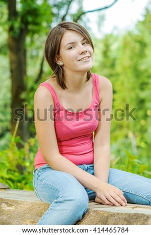Girl outdoors in red vest in woods sitting on log - stock photo
