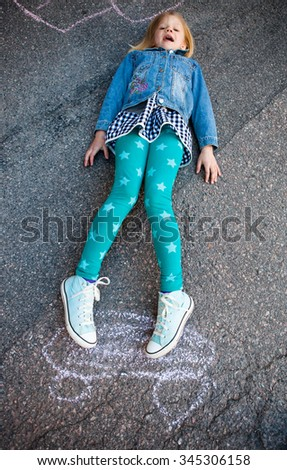 Girl outdoors on asphalt with a skateboard chalk drawing - stock photo