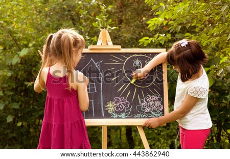 girl paint on a board house, sun, tree. girls in nature - stock photo