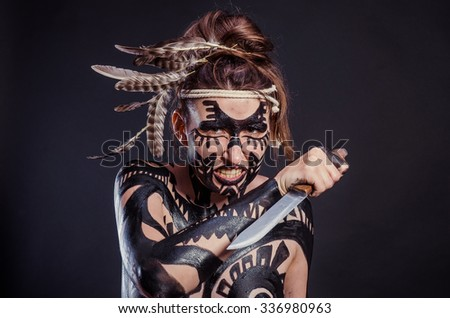 girl painted with black paint in the image of warrior women on a black background