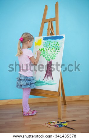 Girl painting her colourful picture on an easel - stock photo