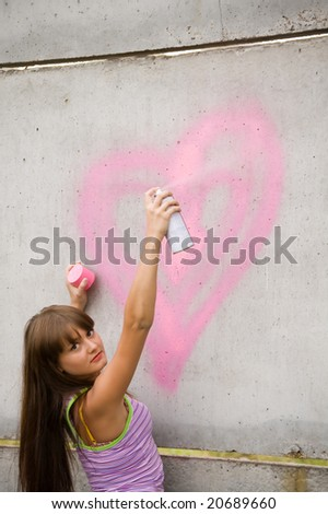 girl painting on the gray and dirty wall - stock photo