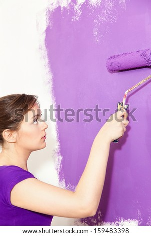 Girl painting wall with purple paint - stock photo