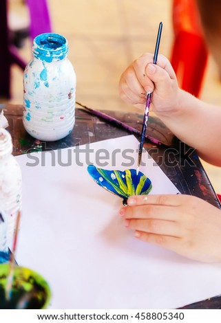 Girl paints a butterfly