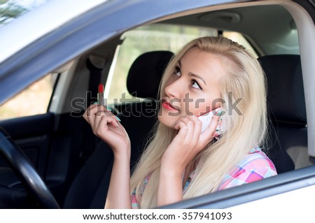 Girl paints her lips and talking while driving