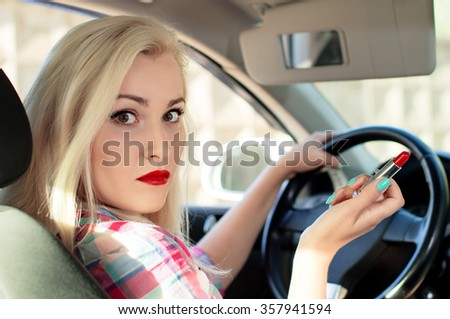 Girl paints her lips while driving a car
