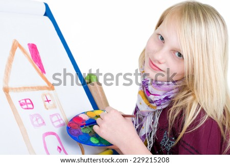 Girl paints on a canvas with brushes a house