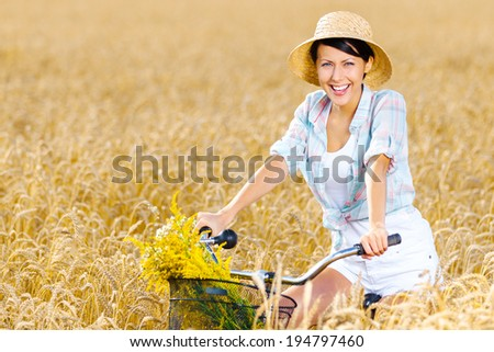 Girl pedals cycle in rye field. Concept of rural lifestyle and sport - stock photo