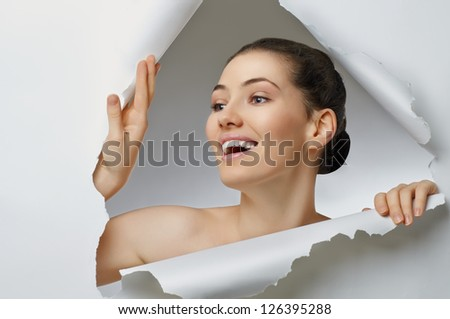 girl peeking out of the hole - stock photo