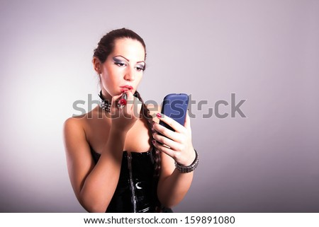 girl performing make up using cell phone like a mirror - stock photo