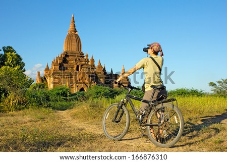 girl photographer on a bicycle takes a picture of the temple in Bagan, Myanmar(Burma) - stock photo