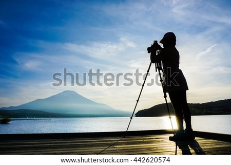 Girl photographer take a photo to Mt.Fuji with tripod at Yamanaka lake, Yamanashi , Japan.