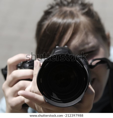 Girl photographer taking pictures with a digital camera - stock photo