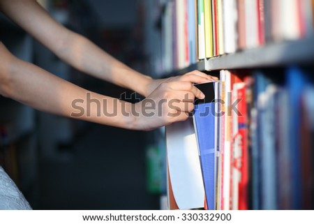 Girl Picking Books in Library