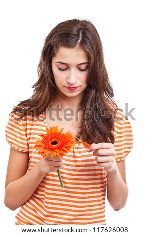 Girl picking the petals from the flower - stock photo