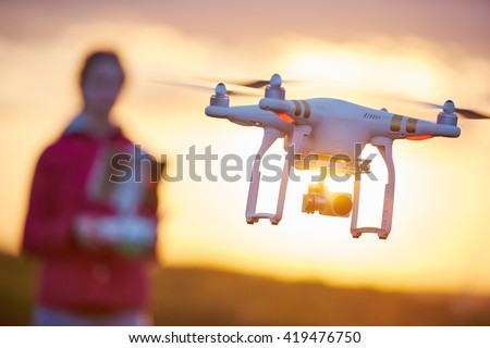 girl piloted copter drone flying at sunset
