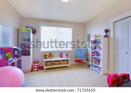 Girl play game room in white and pink with lots of toys - stock photo