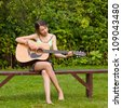 Girl play the guitar and sing outdoors - stock photo