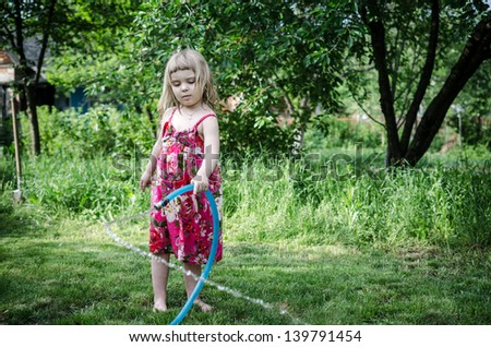 Girl play with water hose - stock photo