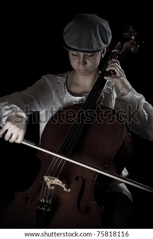 girl playing cello, in black background - stock photo