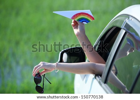 girl playing colorful paper airplane outside window car. - stock photo