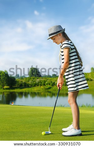 Girl playing golf and hitting by putter on green - stock photo