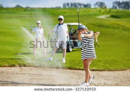 Girl playing golf and  hitting from bunker