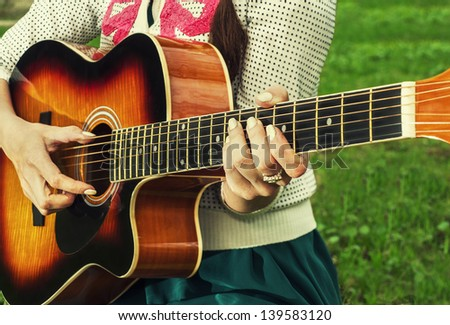 girl playing guitar. close-up - stock photo