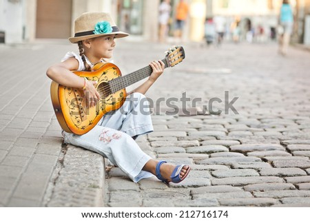 Girl playing guitar on the street - stock photo