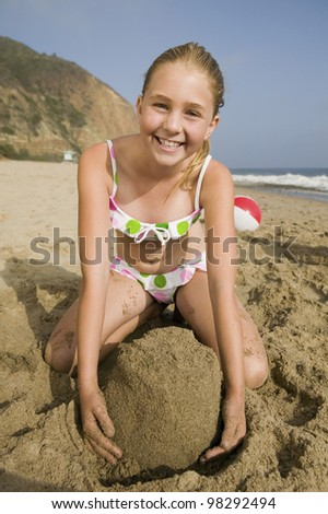 Girl Playing in Sand at Beach - stock photo