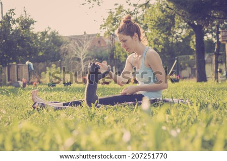 Girl playing in the grass with her kitten, enjoying beautiful summer day - stock photo