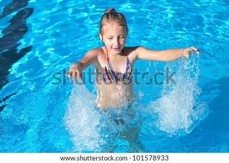 girl playing in the pool with blue clear water
