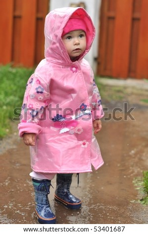 girl playing in the puddle - stock photo