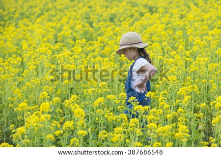 Girl playing in the rape fields